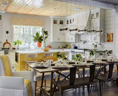 Charming yellow and white u-shaped cottage kitchen features wood and rattan counter stools placed at a yellow island fitted with a microwave drawer fixed beneath a white marble countertop positioned under a blond oak plank ceiling.
