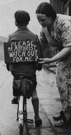 'Taking No Chances' - A mother fastening a notice reading 'Please Mr Motorist, watch out for me', onto her son's back before he sets out on a trial bicycle ride. 1st Jan. 1937. (Photo by Hulton Archive/Getty Images). °