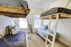 Gorgeous bunk room features staggered floating beds hung from ropes lined with wooden ladders dressed in denim blue coverlets as well as yellow lab print pillows and monogrammed letter pillows alongside ivory painted walls.