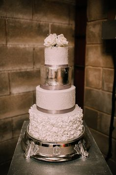Four tier iced wedding cake with silver leaf. Photography by http://www.rosiehardy.com/weddings