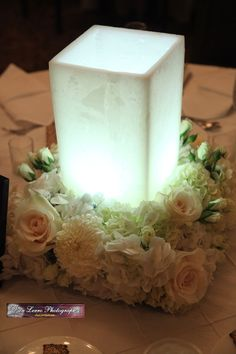 South Jersey Wedding Florist: Leigh Anne and Anthony at The Westin. -  They used the wax luminaries with a square floral design. The luminaries that lined the aisle were moved after the ceremony and placed in the center of the square floral design.  They used white hydrangea, white football mums, ivory roses, and spray roses.