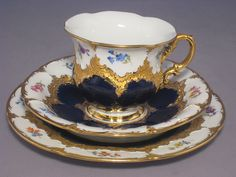 Meissen coffee set B-Form  Ostentatious decor, scattered flowers, colorful, glazed royal blue, bright gold and pale gold (decor 011 099), B-form  with coffee cup and saucer (Form number 15 582) and 19 cm pie plate (form number 15501)  Pfeiffer-time (1924-1934)  minimum (invisible and only sensible) damage to the bottom end of the cup-handle arch