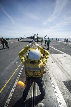 "PHILIPPINE SEA (Aug. 22, 2013) Aviation Boatswain's Mate (Handling) 1st Class Katrina Vong, from Seattle, signals a pilot of an F/A-18E Super Hornet from the ""Dambusters"" of Strike Fighter Squadron (VFA) 195 during taxi on the flight deck of the U.S. Navy's forward-deployed aircraft carrier USS George Washington (CVN 73). (U.S. Navy photo by Mass Communication Specialist 3rd Class Paolo Bayas/Released) most dangerous job. Respect."