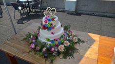 Een prachtige bruidstaart, een gestapelde taart met bovenop 2 chocolade harten! Vanaf boven lopen marsepein bloemen in een slinger naar de onderkant van de taart, en daar gaan de marsepein bloemen dan over in echte bloemen!