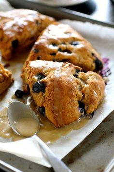 Roasted Banana and Blueberry Scones (makes 6-8 large scones): For the scones- 2 ripe bananas (do not peel them yet-you will roast them with the peels on.) | 2 tablespoons skim milk | 1/2 cup Greek yogurt | 2 and 1/2 cups whole wheat pastry flour | 2 tablespoons cane sugar | 2 tablespoons brown sugar | 2 teaspoons baking powder | 1 teaspoon cinnamon | 1/2 teaspoon salt | 4 tablespoons unsalted butter, cut into pieces | 1 cup fresh blueberries || For the glaze- 1 tablespoons unsalted butter…