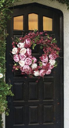 Black front door with large cherry blossom and peonies wreath
