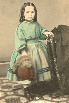 Classic child's frock, gathered bodice and skirt, but long sleeves. Shown with a hat. Tinted.