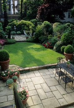 Harpur Garden Images Ltd :: CM200 Small formal town garden with paved patio, dining table and chairs, lawn, containers, borders, arch dividing separate patio at far end of garden. Christopher Masson, London Mrs Kalborg Jerry Harpur Please read our licence terms. All digital images must be destroyed unless otherwise agreed in writing. Photograph by: www.harpurgardenlibrary.com Contact: Harpur Garden Library 44 Roxwell Road Chelmsford Essex CM1 2NB, UK