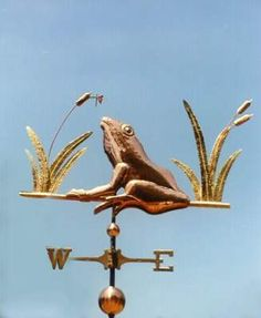 Frog Weather Vane with Dragonfly by West Coast Weather Vanes.  This  handcrafted Frog & Dragonfly weather vane, consists of a copper frog, brass cat tail reeds, a copper seed head and a small brass dragonfly. This customized weather vane has a gold leafed little dragonfly.