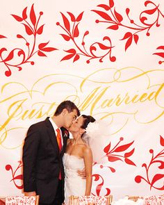 """This """"Just Married"""" banner makes a fitting backdrop for the newlyweds' kiss"""