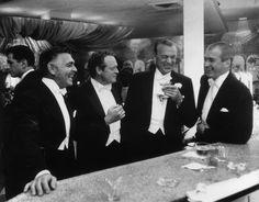 Slim Aarons. Kings of Hollywood: Clark Gable, Van Heflin, Gary Cooper, and James Stewart at Romanoff's in Beverly Hills, 1957.