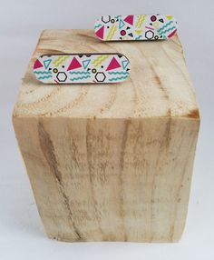 Plywood is cut into a simple shape to create a these statement earrings.The wooden earrings sit on a silver plated earring post. The front of the earrings features jazzy 80s style print.The earrings have been sealed with varnish to protect the wood.All fixtures are silver plated