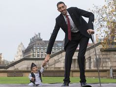 Chandra Bahadur Dangi, from Nepal, the shortest adult to have ever been verified by Guinness World Records, poses for pictures with the world's tallest man Sultan Kosen from Turkey.
