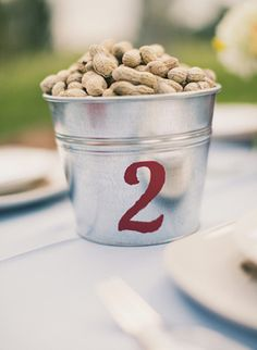 simple galvanized buckets with painted on numbers for table numbers - filled with peanuts!