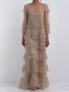 Valentino's ethereal silhouette seen in this beige gown reflects the house's enduring romantic sensibilities. It's expertly crafted in Italy from tulle, and intricately embellished with floral beads and sequins. The high neckline ties at the nape of the neck, echoing the elegant drape that cascades down the frame in lightly ruffled tiers. Sweep your hair up and style with stiletto sandals for a formal event.