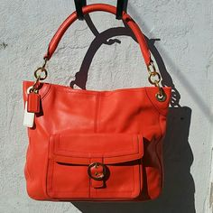 """Coach Penelope Leather Buckle Hobo Excellent condition.  Gorgeous Tangerine color. Zip top closure  Back zipper pocket Front buckle pocket (magnetic snap closure) Back wall zipper pocket Front wall multi function pockets Aporox. 14""""L x 12""""H x 4"""" W There is a small spot on the bottom right near the corner of the bag (See pic 4). It is hardly noticible. This is a great bag. Very hard to find.  Grab this beauty now! Coach Bags Hobos"""
