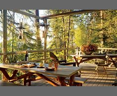 picnic tables and lanterns on the deck in the woods. ***I like the use of tree branches, rather than purchased lumber, for the legs of the table.