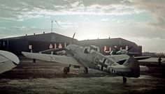 Messerschmitt Bf-109E, S9+HR, of the Luftwaffe's III/ZG1 at sunrise on a well-equipped Italian air base in Libya (Benghazi?/Tripoli-Castel Benito?), Autumn 1942. Note over the hangar's gate an Italian Regia Aeronautica's insignia (three Fasci Littori, Fascist emblems). In front to the hangar an Italian transport plane (S.82 or SM.75) and two German Bf.109.