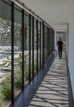 A long hallway with floor-to-ceiling windows connects the living areas of this modern house to the bedrooms. A long hallway with floor-to-ceiling windows connects the living areas of this modern house to the bedrooms. New Modern House, Modern Mansion, Long Hallway, Modern Hallway, Casa Loft, Corridor Design, Modern Villa Design, Long House, Floor To Ceiling Windows