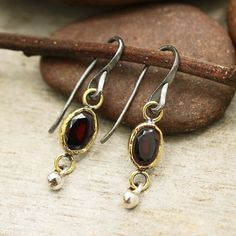 Oval faceted garnet earrings in brass bezel setting and silver beads decorated below with oxidized sterling silver hooks