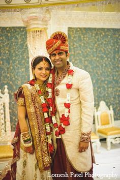 Traditional Indian bride and groom wearing bridal saree and the groom wearing a sherwani