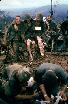 October 1966 - American Marines aid wounded comrades during Operation Prairie near the DMZ during the Vietnam War.