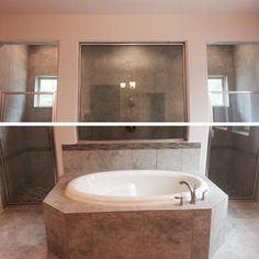 Huge walk-in shower wrapped behind bathtub