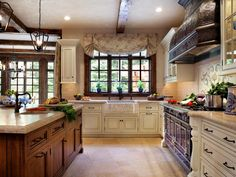 This spacious French country kitchen features gorgeous ceiling beams made of reclaimed wood, an ornate stove hood and a gas range. Cream cabinetry contrasts beautifully against the warm wood in the kitchen island and the window panes above the sink.