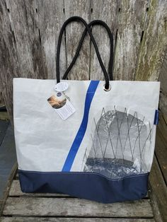 """By the Bay Creations Beach Tote made from retired sail™.These sails have been naturally weathered from their voyages on the Chesapeake Bay. The original stitching is used to create a classic sail bag that anyone can enjoy while looking stylish on their journeys.This listing is for a Beach Tote that has a marine grade Sunbrella fabric bottom.The approx 19""""W x 18""""H bag makes a perfect land or water companion to carry your essentials. The rope handles have a 10"""" drop creating a comfortable fit Sailing Outfit, Chesapeake Bay, Sunbrella Fabric, St Michael, Bag Making, Stitching, Essentials, Drop, Tote Bag"""