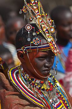Young Masai bride, Kenya. The number of beaded strings hanging from the collar indicates the number of animals that will be given by the groom's family to the bride's family. (V)