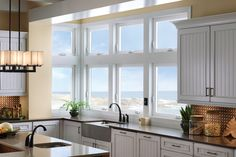 Thick bold white window frames can be a unique look for the kitchen space.  These windows can be opened easily and provide a beautiful view. Featured: A combination of Tuscany® Series awning and casement windows.