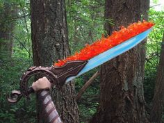 """One Sword of Fire and Ice!  Round Two of the TranspArt contest has come to a close. We had to work with a medium sheet each of Worbla and Transpart as well as two colors of iDye Poly (I got red and blue) and the theme """"Out of This World"""". I decided to go back to my roots and remade one of my first ever props.  Both blades were made from a base of Transpart that was heat welded together. The ice blade was filled with resin and the fire blade was covered with dyed transpart to look like fire…"""