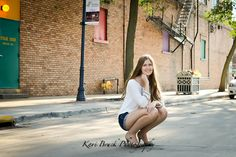 2014 High School Senior girl for posing picture ideas. Senior girl posing in an urban or downtown setting with brick building background. High school senior session pose inspiration for senior pictures.