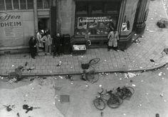 Tweede Wereldoorlog : Bevrijding, schietpartij op de Dam : Na deze beruchte beschieting staan mensen dekking te zoeken tegen de huizen / panden langs de Dam, oa. voor de gevel van reisbureau Lisonne - Lindeman. Een aantal fietsen ligt op de uitgestorven straat. Nederland, Amsterdam, 7 mei 1945.