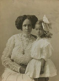 Images capture pioneering African-Americans of the This image shows a mother and daughter wearing white dresses. The woman looks as the camera while the girl stands next to her