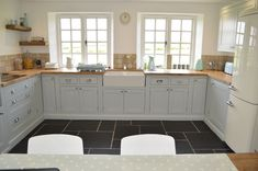 A beautiful example of one of our handmade kitchens in a Soft Grey with Oak worktops and a double butler sink.