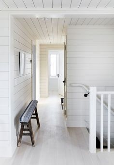 Mann wanted the home to feel nautically inspired without resorting to any beach house clichés. Shiplap walls and bleached flooring, seen in the hallway, convey this desired nod to coastal design in an elegant and subtle way. The bench is vintage and covered in a striped linen fabric.