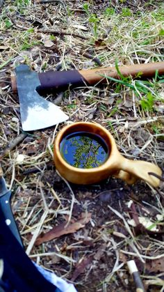 Les Stroud Bushman axe and a kuksa. Blue sky and green tree reflection in the coffee mug caught my eye.