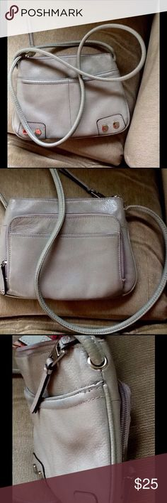 """Tignanello leather small messenger/crossb handbag Awesome Tignanello small messenger/cross-body leather light gray handbag  Very good condition inside and out  Inside the bag there is one large zip pocket  Outside the bag there is a large zippered compart me with space for credit cards, driving license,  etc.  Beautiful gray leather bag  Some signs of wear but minimal, please examine photos. Measurements are approximates  Height 7.5"""" Length 10"""" Depth 1"""" Strap drop 24"""" and not adjustable…"""
