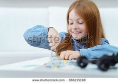 Pretty little redhead girl sitting at a table at home working with a screwdriver with a beaming smile