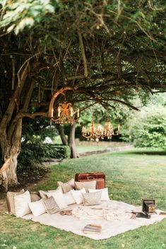 a beautiful area under the trees with hanging chandeliers and a picnic blanket as a place for guests to take photos