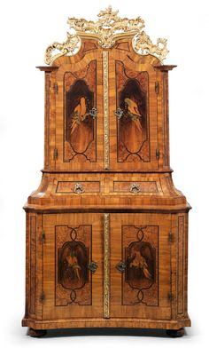 Splendid Baroque cabinet, Austria, circa 1750. A cabinet a trois corps, veneered in walnut and decorated with high quality marquetry panels and bands as well as four parrots rendered in partly burnt, dyed and engraved fine woods. The serpentine and concave lower section has two doors, the central section has two drawers and the upper section has two doors and a pierced, carved and gold painted cresting. 207 x 108 x 60 cm