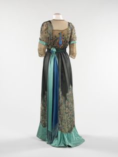 """Evening Dress (back view), Weeks: 1910, French, silk, metal. """"Associated with royalty and symbolizing beauty, immortality and exoticism, the peacock has long been a favorite motif of artists. Particularly during the Art Nouveau movement, designers incorporated the birds into their work, inspired by the creatures' sinuous bodies and showy feathers."""""""