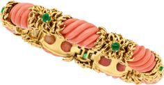 Coral, Emerald, Gold Bracelet, Tiffany & Co.  The bracelet features carved coral measuring 18.00 x 11.00 mm, enhanced by round-shaped emeralds weighing a total of approximately 1.00 carat, set in 18k gold, marked Tiffany & Co.