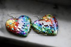 Just in time for the holidays, this pair of big statement resin earrings I made features shiny mirror image unicorn silhouettes backed with shards of