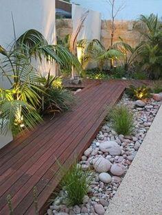 Jardins secs dans le court d'une maison composés de rochers, mousses et graviers