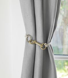 "DIY in a Day..  Make Rugged-Chic Tiebacks  Interior designer Annie Selke dreamed up this frill- (and drill-) free way to corral drapes: Just combine a swiveleye snap hook, key ring, and cord. (Brass snap hook, $2.37; 1½"" ring, 97 cents; 1/8"" cord, $3.92 for 45'; homedepot .com for stores)"