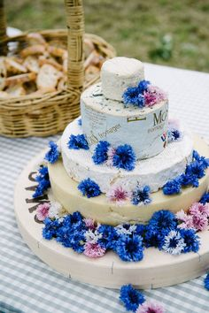 Cheese-wheel cake adorned with edible flowers