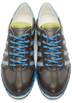 Grey Striped Leather Sneakers by Dolce & Gabbana. Low-top sneakers in grey. Grained leather trim throughout in dark grey. Round toe. Lace-up closure in cornflower blue. Matching lace trim at welt. Buffed leather trim in powder blue at heel collar and sides. Grained leather logo patch at tongue in chartreuse. http://www.zocko.com/z/JGuoZ