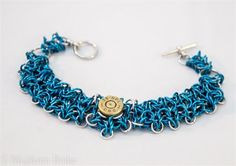 Bracelet is made up of Individual Anodized Aluminum Jump rings in Silver and Blue topped with a 38 special Shell casing  toggle clasp. This would make a grate gift for any woman who is a county girl at heart or just likes some thing different  Unique.  Bracelet size: Length 7 1/2 inches Width 1/2 inch  Bracelet will come in a nice gift box Like the one in the photos above.  ** All Shells that are used on our bullet Jewelry have been shot and may show signs of that fact. I do my best to…